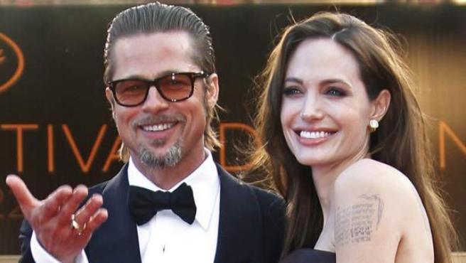 Angelina Jolie y Brad Pitt, durante una alfombra roja en el Festival de Cannes. La actriz muestra en su brazo uno de sus famosos tatuajes.