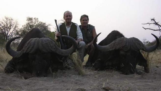 Imagen publicada en la web de Rann Safaris en la que el rey posa con dos búfalos muertos.