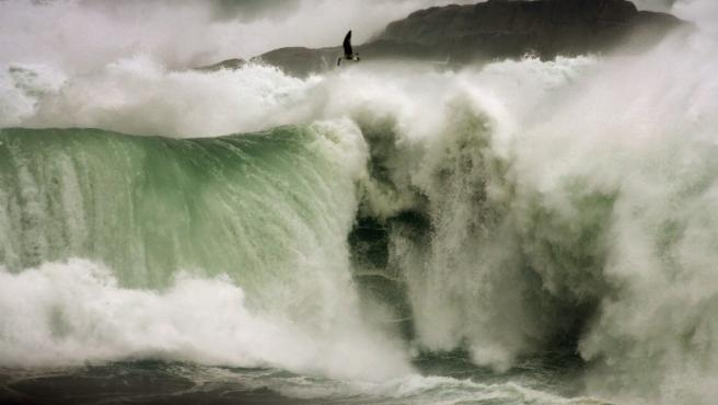 Una gran ola rompe contra las rocas a la entrada de la Ría de A Coruña, en la zona de Mera, en donde se mantiene activado el nivel de alerta roja en el mar y la alerta de nivel amarillo en tierra a causa del fuerte viento. La flota gallega permanece amarrada a puerto debido a las condiciones del mar.