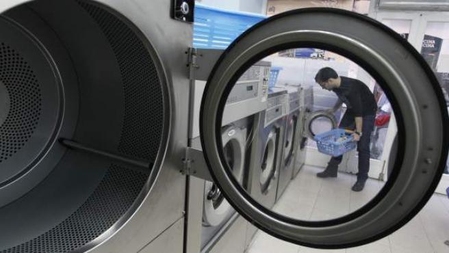Un cliente se dispone a lavar su ropa en una lavandería autoservicio.