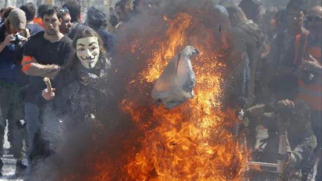 Un grupo de manifestantes, algunos enmascarados, realizaron pequeñas hogueras en el Paseo de Gracia de Barcelona para protestar contra la reforma laboral durante la jornada de huelga del 29-M convocada en toda España.