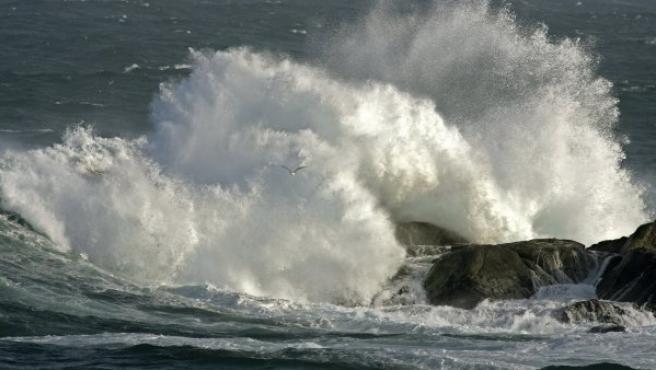 Una ola rompe contra las rocas de la Ría de A Coruña, a la altura de la Torre de Hércules.