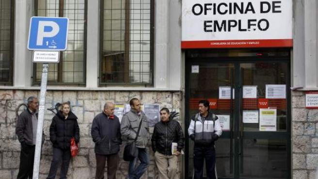 Un grupo de personas hacen cola frente a una oficina de empleo en Madrid.
