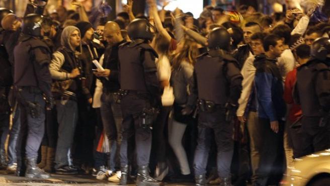 Miembros de la policia nacional impiden que seguidores del Real Madrid invadan la calzada, durante la celebración de los aficionados blancos en la madrileña plaza de Cibeles.