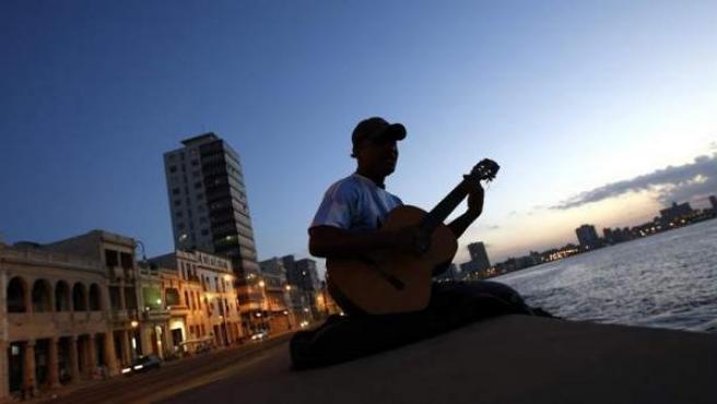 Un hombre toca la guitarra sentado en el muro del malecón en La Habana (Cuba).