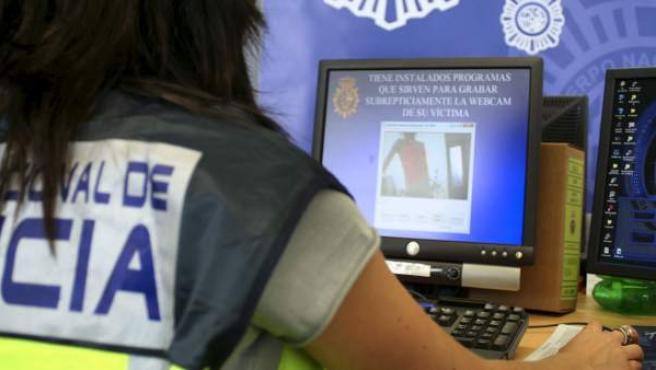 Una agente de policía, frente a un ordenador.