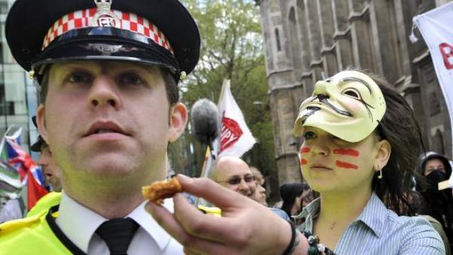 Una manifestante de Occupy London ofrece comida a un policía.
