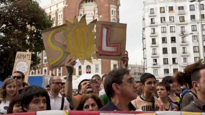 """Un manifestante de Madrid lleva tres carteles que conforman la palabra """"Sol""""."""