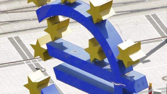 Dos peatones caminan junto a un símbolo del euro en el recinto del Banco Central Europeo en Fráncfort (Alemania).