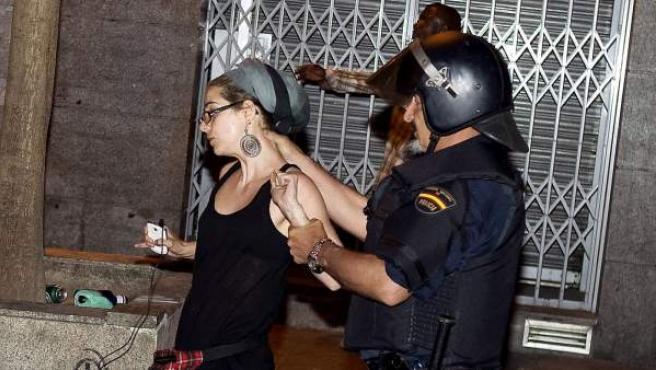 Un policía aparta a una chica durante el desalojo de los 'indignados' durnate la madrugada del lunes 14-M.