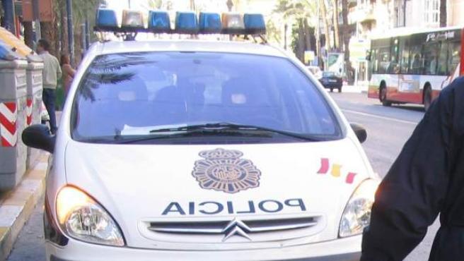 Un agente de policía, junto a un coche patrulla.