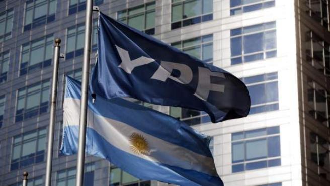 Una bandera argentina junto a una bandera de YPF en la sede de la empresa petrolera en Buenos Aires.