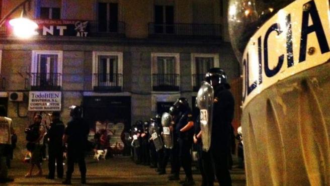 La policía forma un cordón en la plaza de Tirso de Molina, Madrid, en la marcha nocturna de aniversario del 15M.