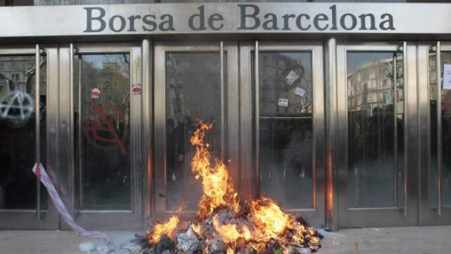 Un piquete de unas mil personas, algunas con los rostros cubiertos, ha provocado durante el desarollo de la huelga general del 29-M un pequeño incendio frente a la Bolsa de Barcelona tras realizar pintadas e intentar varias veces derribar sus puertas.