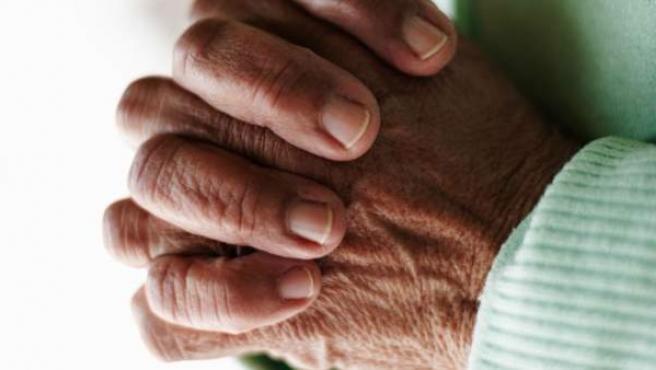 Una anciana reza juntando las manos.