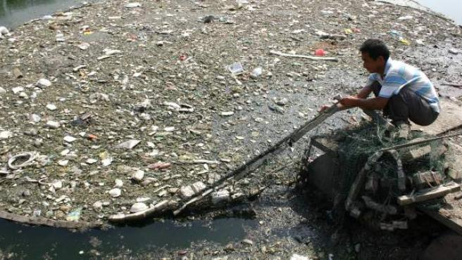 Un hombre limpia la basura acumulada en un canal de Pekín.