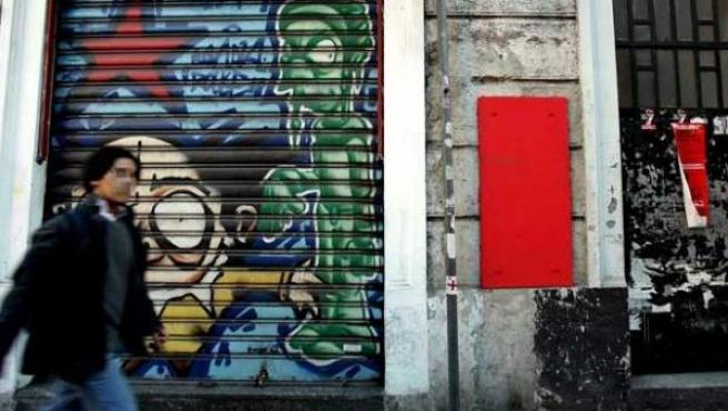 """Un joven pasa ante un centro social llamado """"Panetteria Okkupata"""" en Milán."""