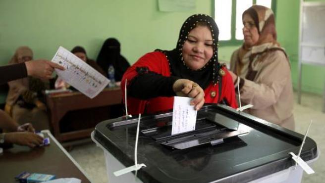 Una mujer egipcia deposita su voto en un colegio electoral.