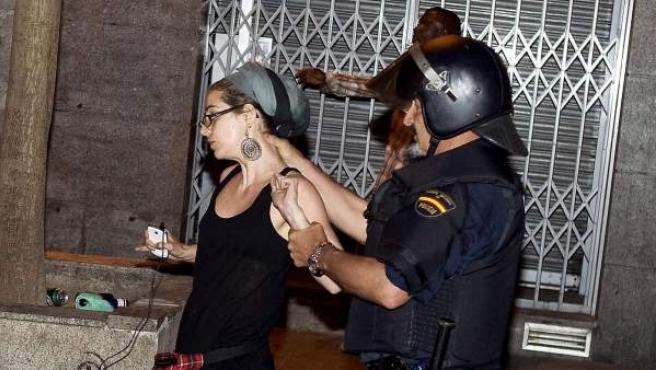 Un policía detiene a una joven durante uno de los desalojos de la Puerta del Sol con motivo del aniversario del 15-M.