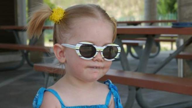 Una niña, con gafas de sol protegiendo sus ojos.