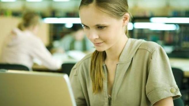 Una chica trabaja con su portátil.