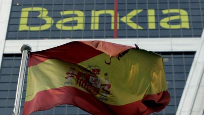 La bandera española, ante una instalación de Bankia.