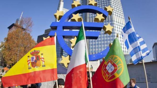 Un español, un italiano, un portugués y un griego ondean las banderas de sus países frente a la sede del BCE en Fráncfort, Alemania.