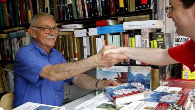 El escritor Eduardo Mendoza saluda a sus lectores y firma ejemplares de sus libros en la Feria del Libro de Madrid.
