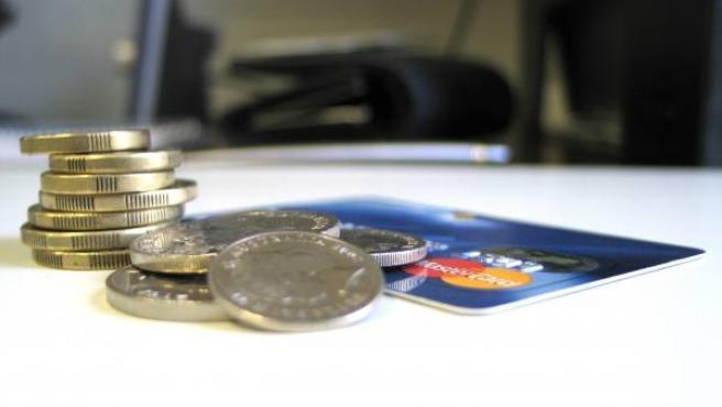 Varias monedas y una tarjeta de crédito.