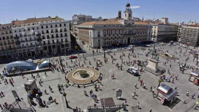 Panorámica de la Puerta del Sol con el edificio de la Real Casa de Correos, sede del Gobierno regional, en la parte superior derecha.