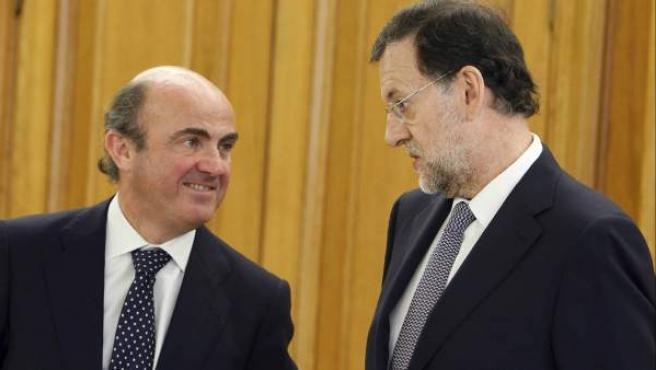 El presidente del Gobierno, Mariano Rajoy (d), conversa con el ministro de Economía, Luis de Guindos (i)