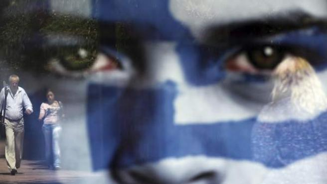 Peatones se reflejan en un cartel electoral del partido Alianza Democrática, en Atenas, Grecia.