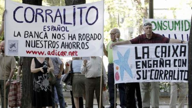 Varias personas despliegan pancartas ante la sede de la Caixa en Madrid durante una concentración convocada por la Asociación de Usuarios de Bancos, Cajas y Seguros para protestar por la comercialización irregular de participaciones preferentes.