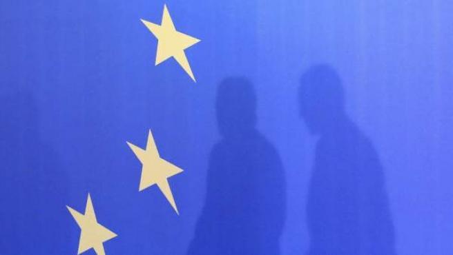 Las sombras del primer ministro rumano, Victor Ponta (dcha), y del presidente de la Comisión Europea, José Manuel Durao Barroso, proyectadas sobre una bandera de la Unión Europea.