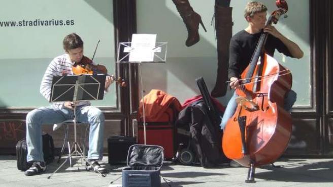 Dos músicos tocan en plena calle.