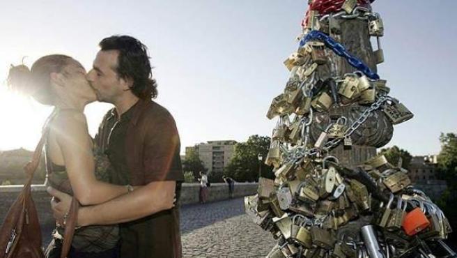 Una pareja besándose frente a una farola repleta de candados en el puente Milvio de Roma, Italia.