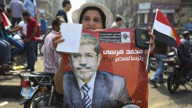 Una simpatizante del candidato de los Hermanos Musulmanes, Mohamed Morsi, sujeta un cartel electoral en la plaza Tahrir, tras saber el resultado de las elecciones presidenciales en El Cairo, Egipto.