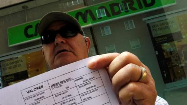 Un hombre afectado por las preferentes muestra una denuncia a Caja Madrid.