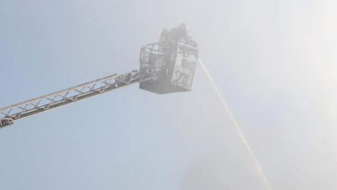 Un bombero trabaja en el fuego en la nave de Salvador Bachiller, en Arganda del Rey (Madrid).