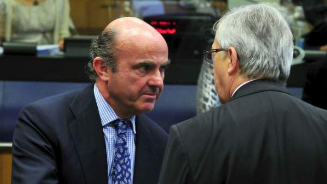 El ministro español de Economía, Luis de Guindos, conversa con el presidente del Eurogrupo, Jean Claude Juncker.