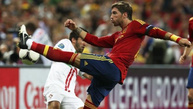 El jugador portugués Joao Moutinho (i) pelea por el balón con el español Sergio Ramos (d).