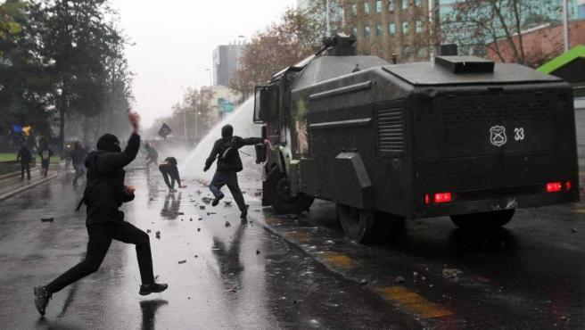 Manifestantes atacan un carro lanza-aguas (comúnmente llamado 'Guanaco', animal que escupe cuando se enoja) el 28 de junio de 2012, en la marcha que fue convocada por el Confederación de Estudiantes de Chile (Confech).
