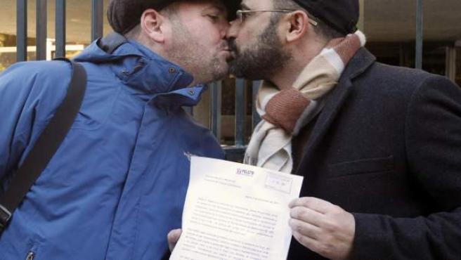 Antonio, presidente de la FELGTB, besa a su marido con una carta al Tribunal Constitucional para que se pronuncie sobre la constitucionalidad de la ley que regula estos enlaces.