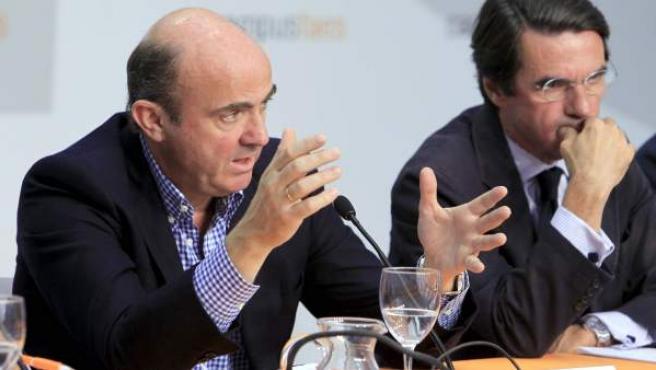 El ministro de Economía y Competitividad, Luis de Guindos (i), durante su intervención en el Campus de la Fundación para el Análisis y los Estudios Sociales (FAES). A su lado, el ex presidente del Gobierno y presidente de FAES, José María Aznar.