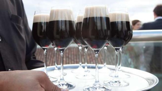 Una bandeja con copas de cerveza negra