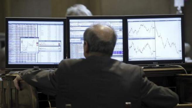 Un visitante observa los monitores de la Bolsa, donde el Ibex 35 se hundió este viernes un 3,1%.
