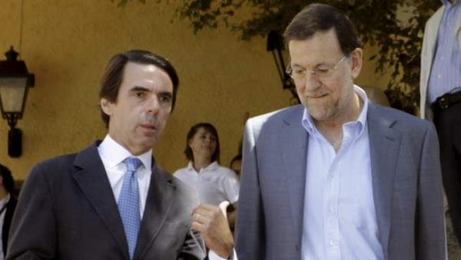 El jefe del Ejecutivo, Mariano Rajoy (d), y el presidente de FAES, José María Aznar, conversan poco antes de clausurar en Navacerrada el IX Campus de verano de la citada fundación.