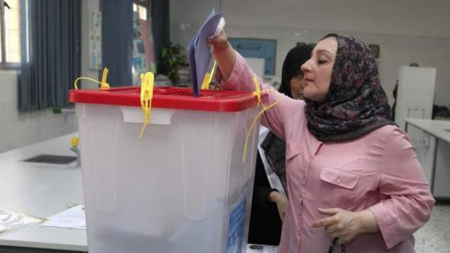 Una mujer libia vota durante las elecciones legislativas que celebra el país.