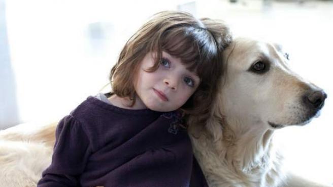 Una niña pequeña abraza a su perro.