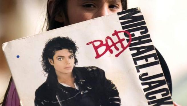 Un niño muestra el disco de Michael Jackson 'Bad'.